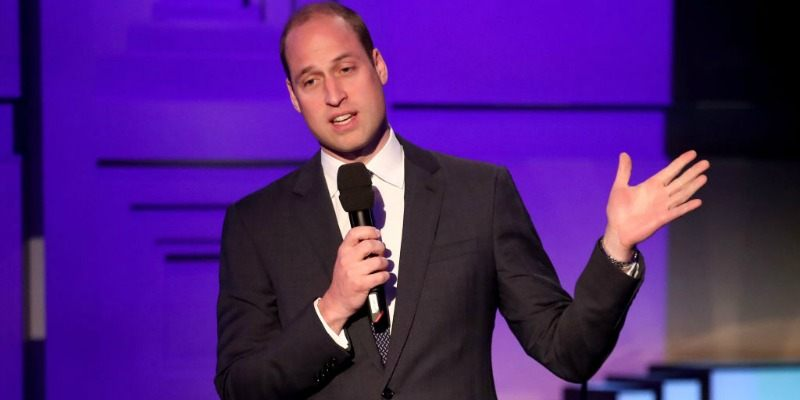 Prince William holds a microphone while standing in a suit.