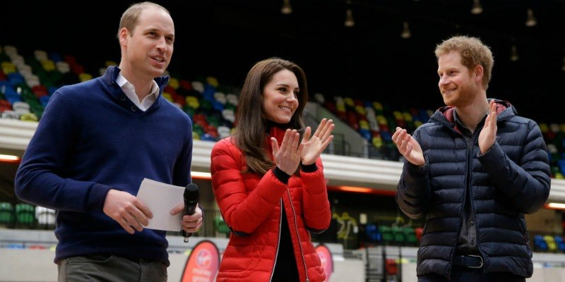Prince William, Duchess Kate Middleton, and Prince Harry are clapping at a stadium full of people.