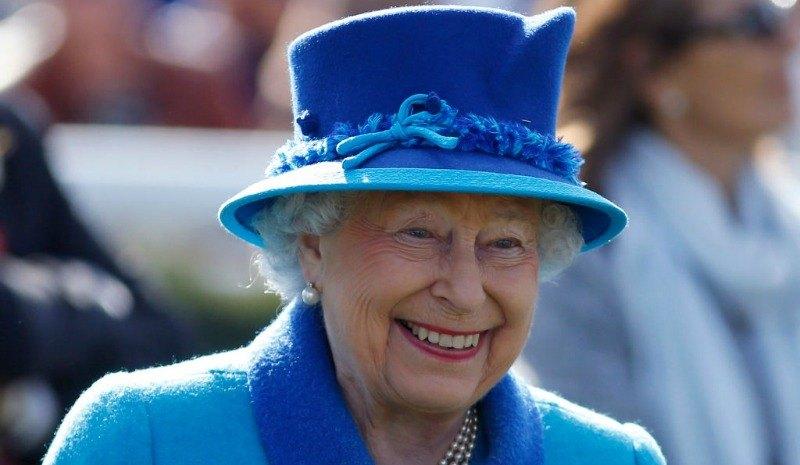 Queen Elizabeth II is wearing a blue suit dress and a hat.
