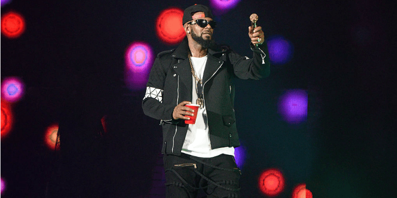 R. Kelly is on stage holding a microphone and red cup.