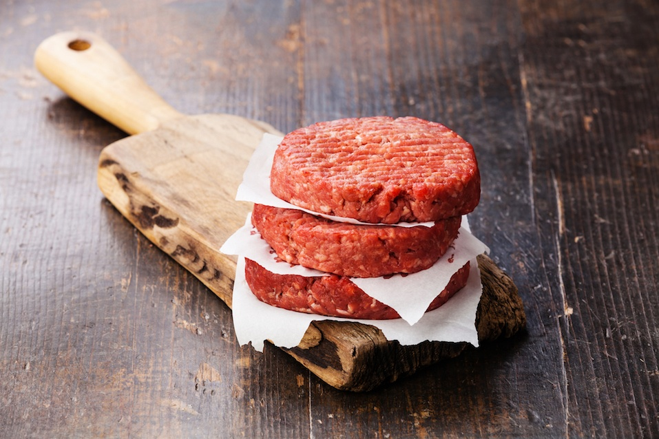 Raw Ground beef meat Burger steak cutlets on cutting board on dark wooden background