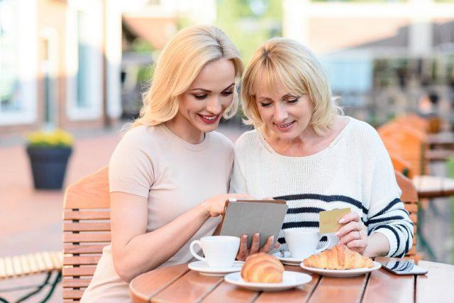 Cheerful mother and daughter are using tablet and smiling.