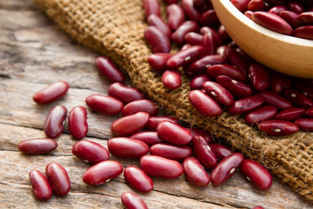Red beans spread out on a wooden table.