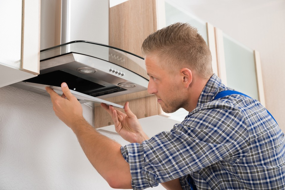 repairman fixing stove hood