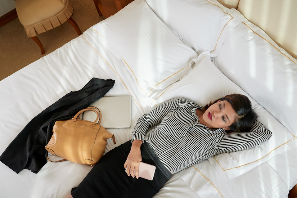 Tired business lady resting in bed after difficult day