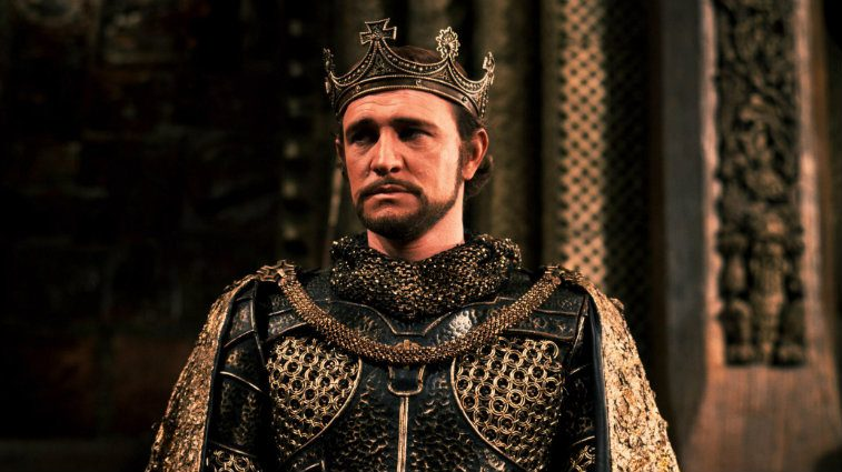 Richard Harris wearing armor and a crown while looking troubled in Camelot