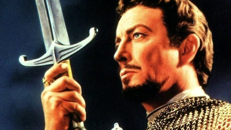 Robert Taylor holding a sword and gazing off into the distance in Knights of the Round Table