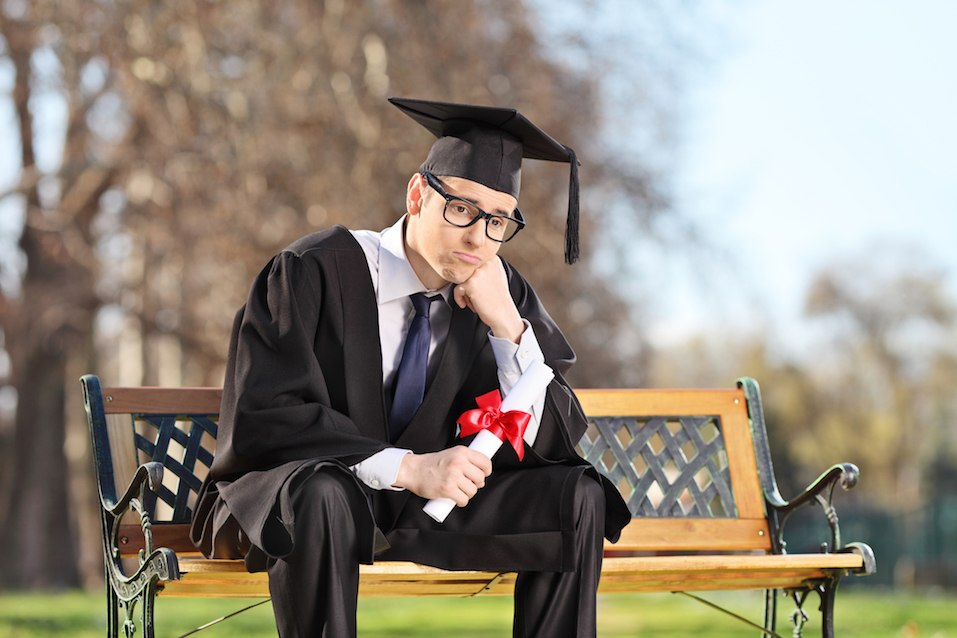 Sad college grad sitting on a bench in park