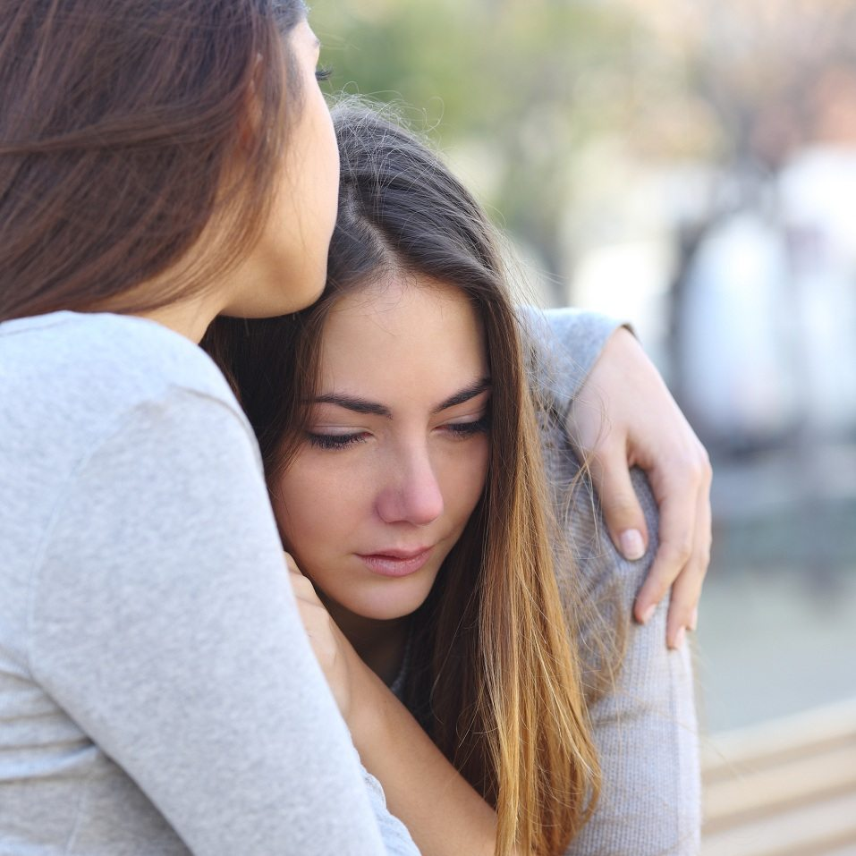 Sad girl crying and a friend comforting her outdoors