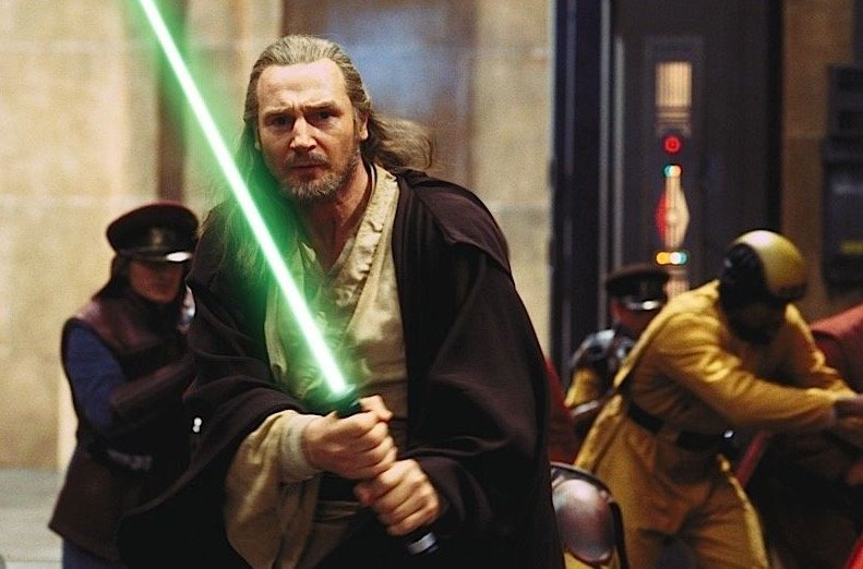 Qui Gon holds his lightsaber out in front of his body in The Phantom Menace