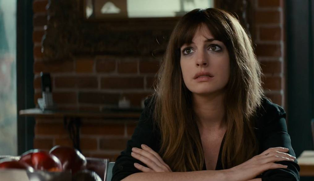 Anne Hathaway sitting at a table in Colossal.