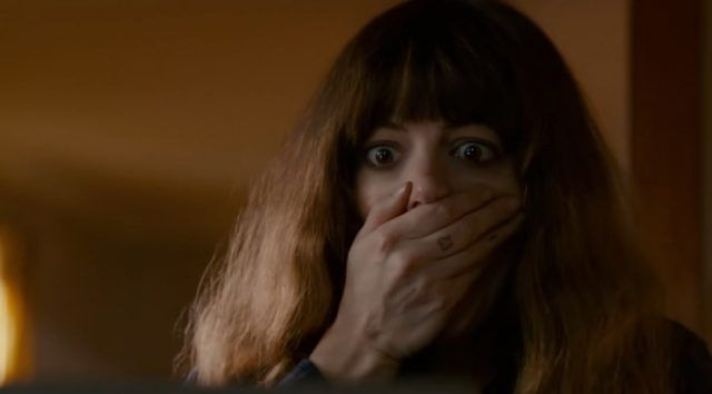 Anne Hathaway with her hand to her mouth looking shocked