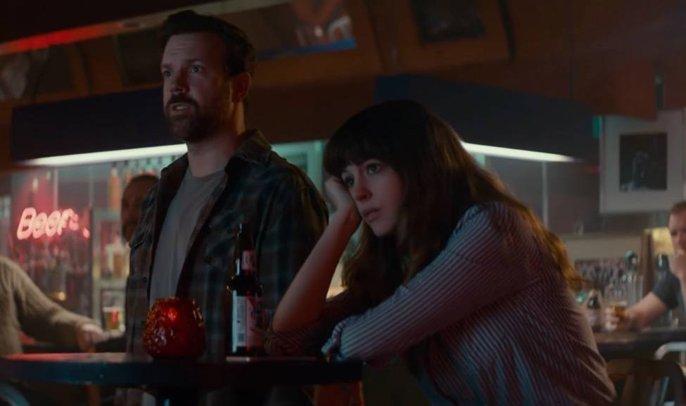 Jason Sudeikis and Anne Hathaway together in a bar, watching TV that's out of the frame