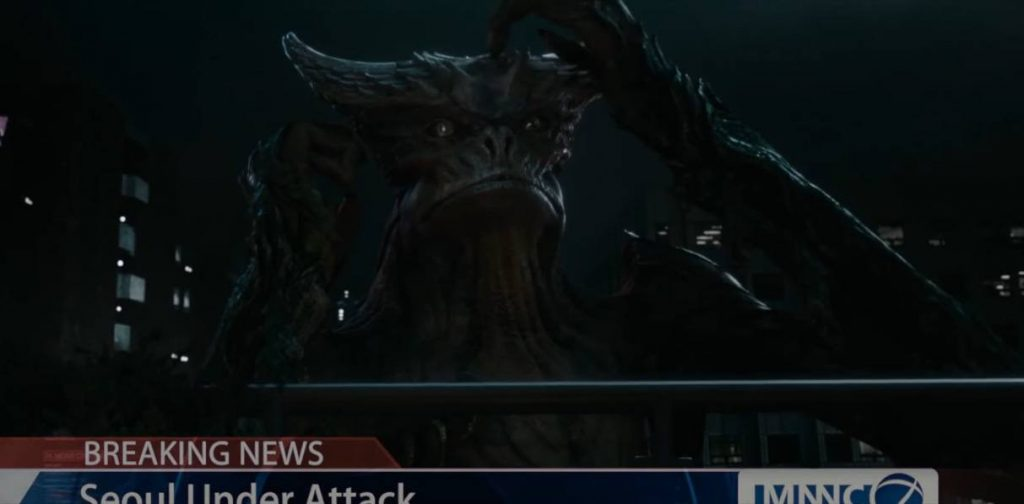 The monster in Colossal scratching its head while on a newscast