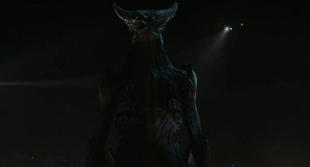 The monster from Colossal standing with its arms at either side