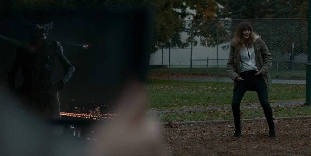 Anne Hathaway dancing on a playground, with a monster on an iPad in the foreground