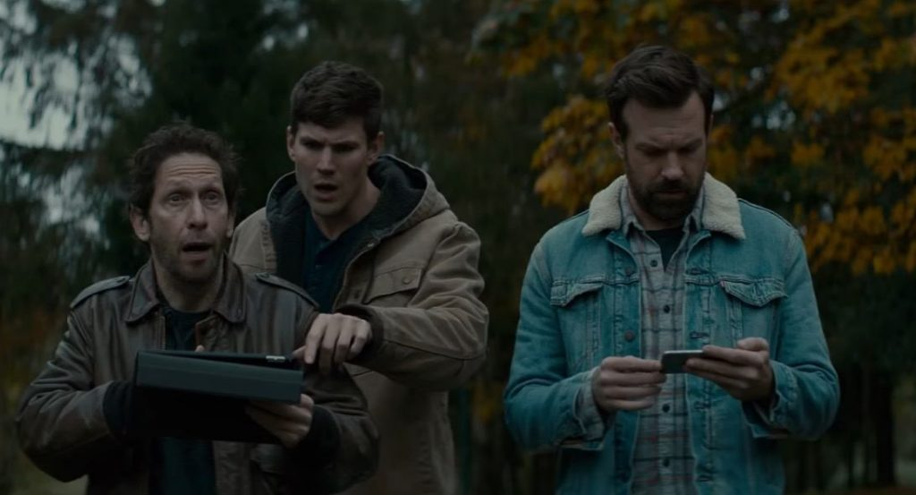 The cast of Colossal in a park, looking down at an iPad screen together