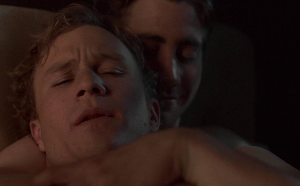 A close up on Jake Gyllenhaal and Heath Ledger sitting together in bed, embracing each other