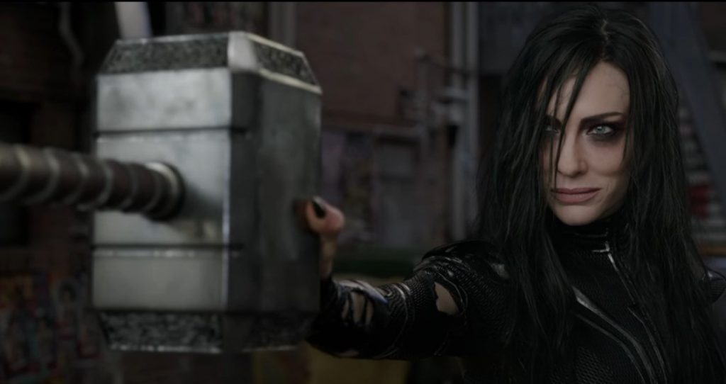 Hela holds Thor's hammer out in front, looking to the left of the frame