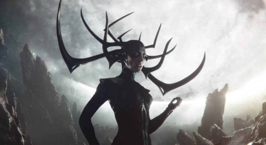Hela with her left hand up, and her antler-helmet on