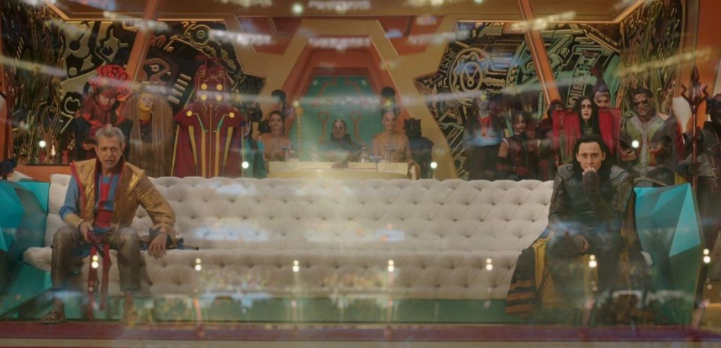 Grandmaster and Loki sitting on either side a long white couch