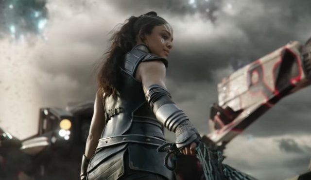 Tessa Thompson wearing armor, with her right hand out.