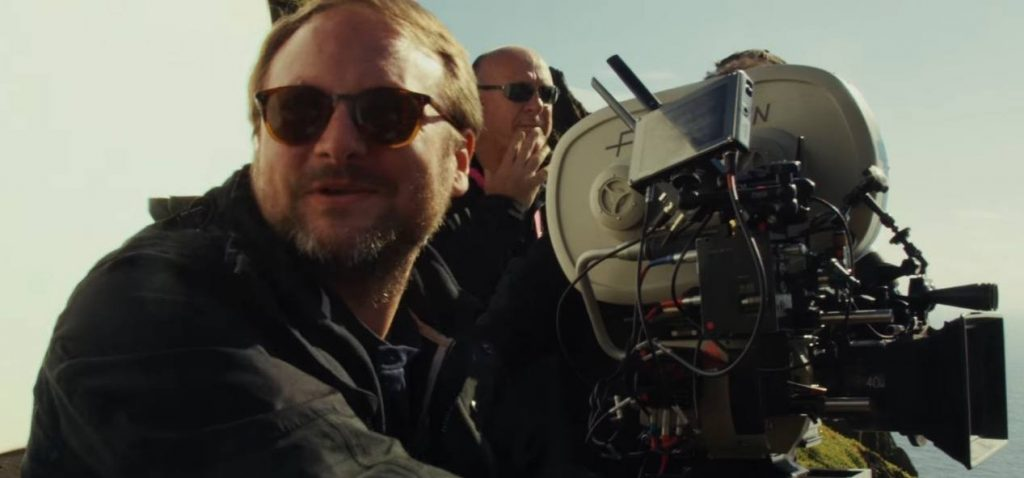 Rian Johnson smiles, sitting next to a camera