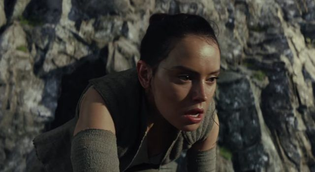 Rey bent over, sweaty and panting in front of a mountain.