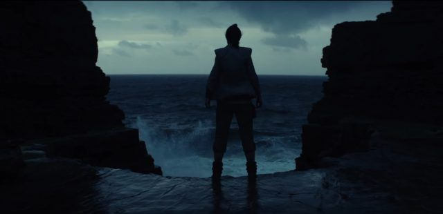 Rey stands in front of a cliff face, with waves crashing in front of her