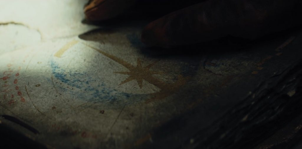 A hand touches a book bearing the symbol of the Jedi Order