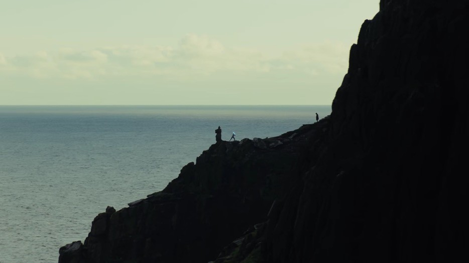 A long shot of Rey training with a lightsaber on a cliff face, while Luke patiently looks on