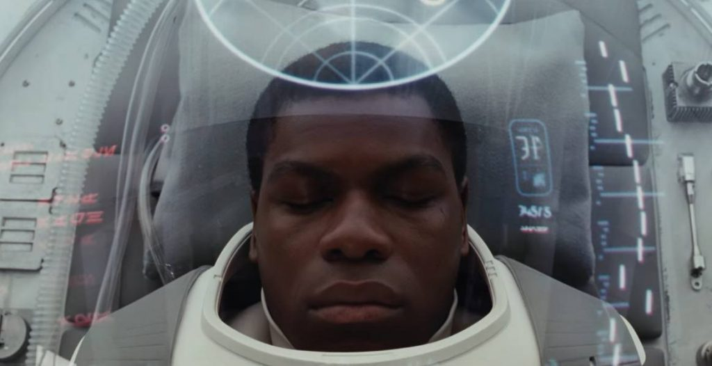 Finn asleep, in what looks to be some sort of mechanical recovery suit