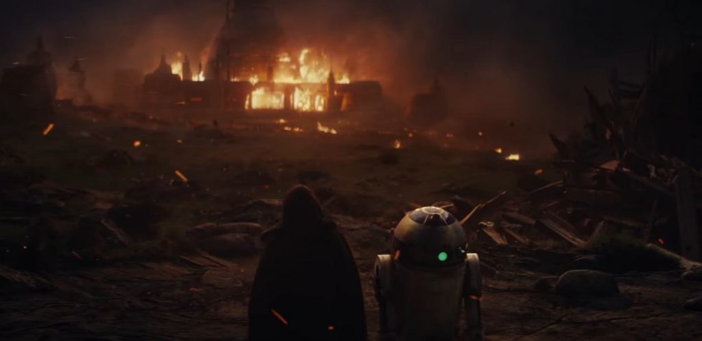 Luke and R2D2 look on at a house on fire, amidst a ruin