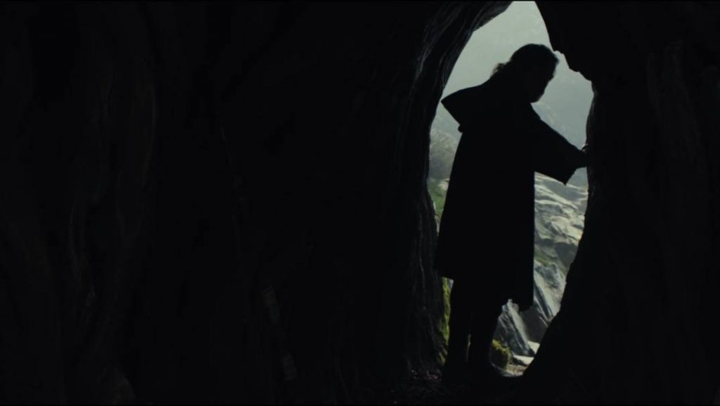 Luke looking back into a cave, silhouetted