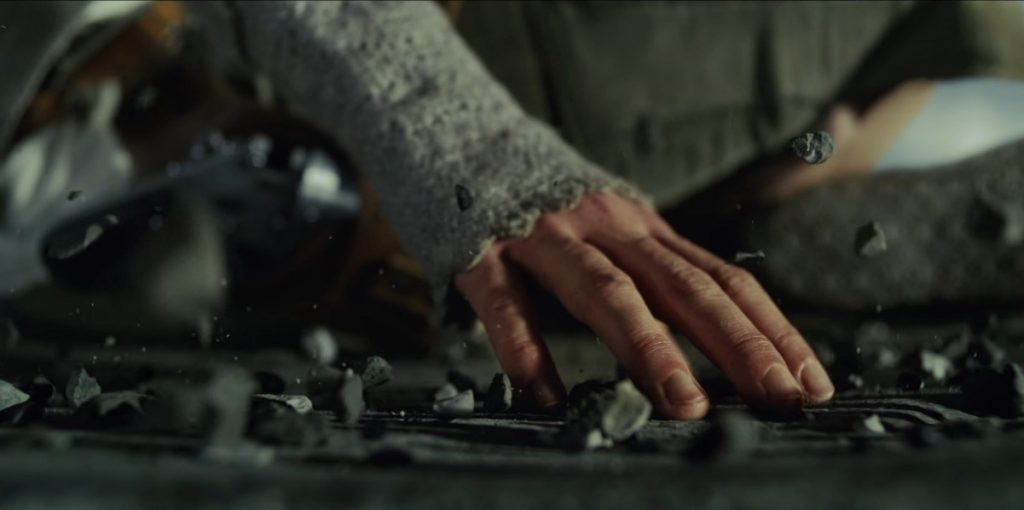 Rey with one hand placed on the ground, lifting a group of pebbles together with the Force