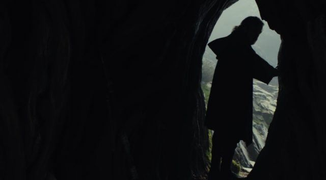 Luke stands silhouetted at the entrance to a cave.