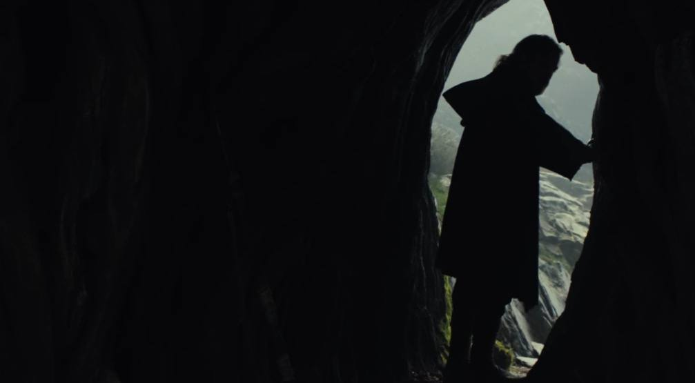 Luke stands silhouetted at the entrance to a cave
