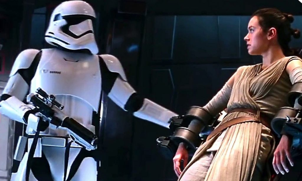 A Stormtrooper with his arm out, while Rey is shackled to a platform