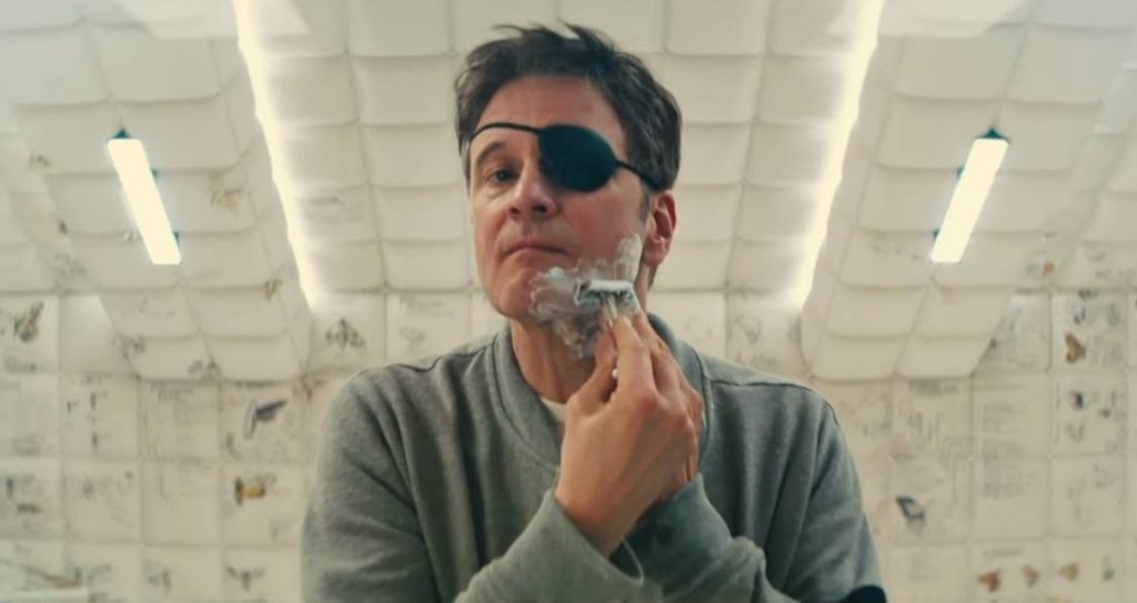 Colin Firth shaving, wearing a white sweatshirt and an eyepatch
