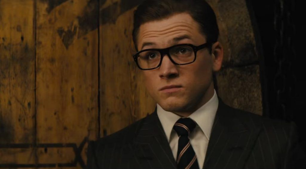 Taron Egerton with his eyebrows raised, wearing a suit