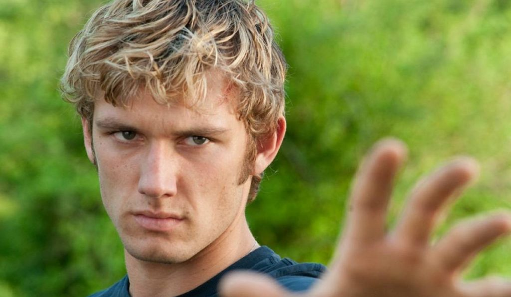 Alex Pettyfer with his hand out, scowling