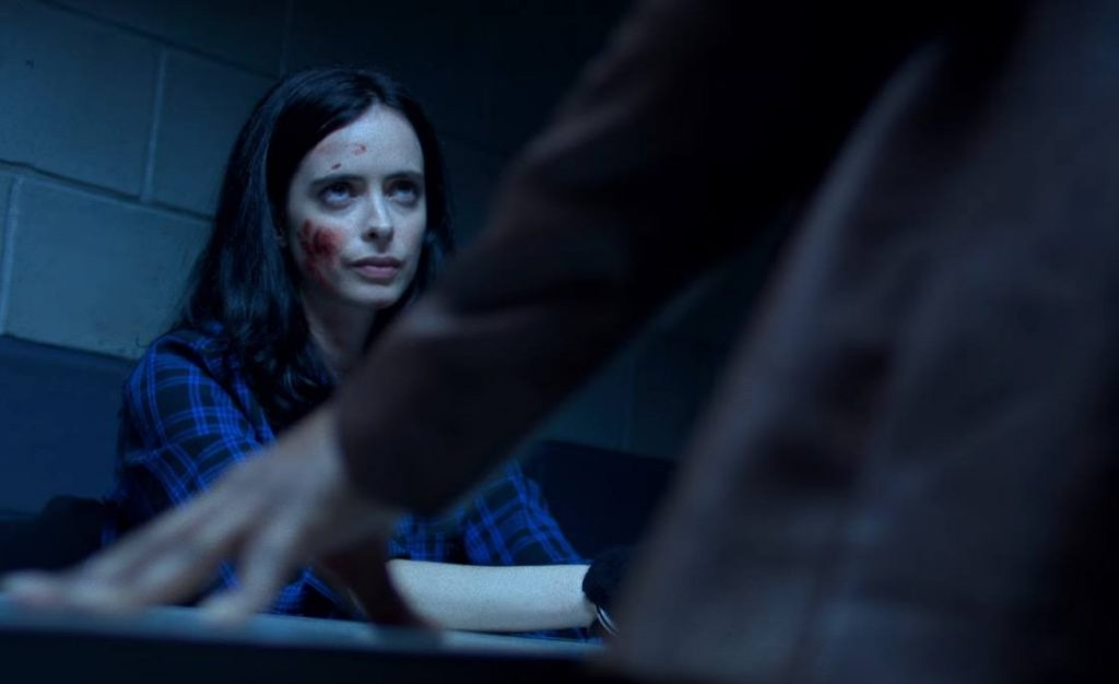 Jessica Jones scowling, sitting in an interrogation room