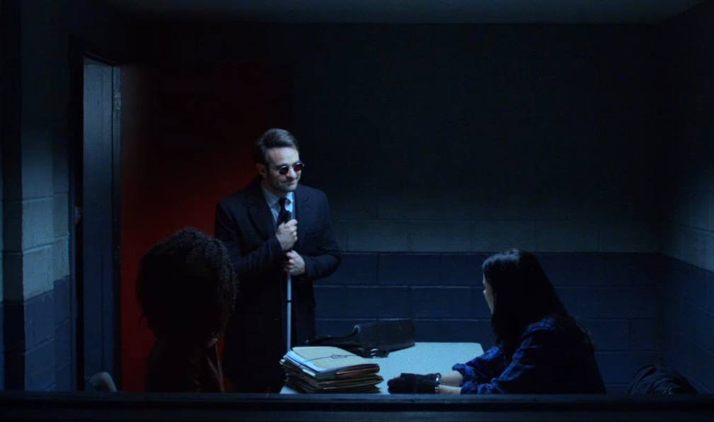 Matt Murdock smiling in an interrogation room with Jessica Jones