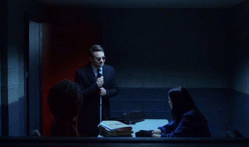 Matt Murdock smiling in an interrogation room with Jessica Jones