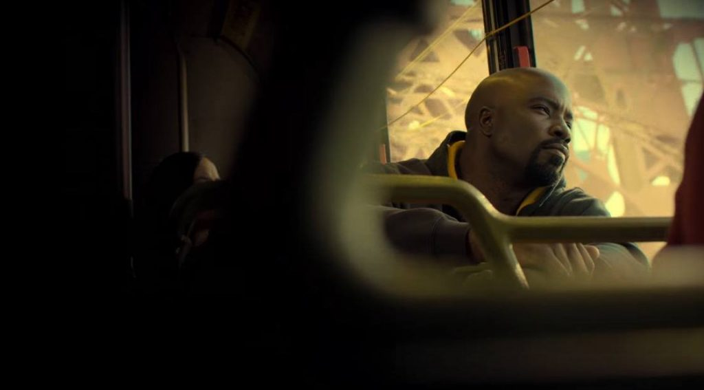 Luke Cage sitting on a bus, looking out a window