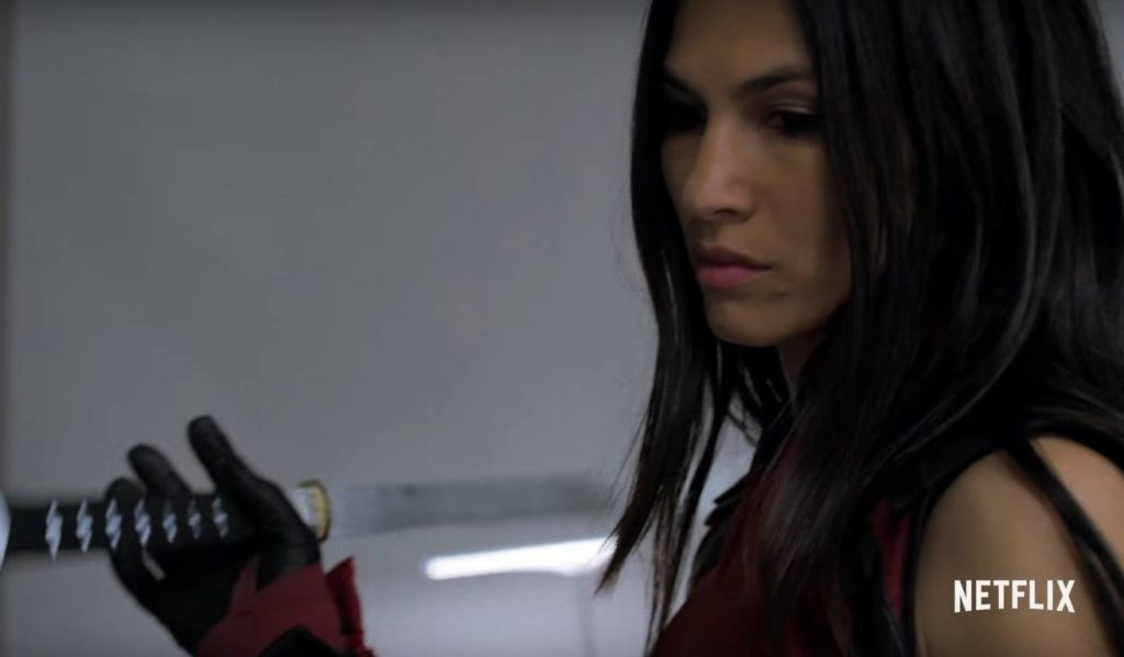 Elektra holding a katana, looking down, and preparing to fight