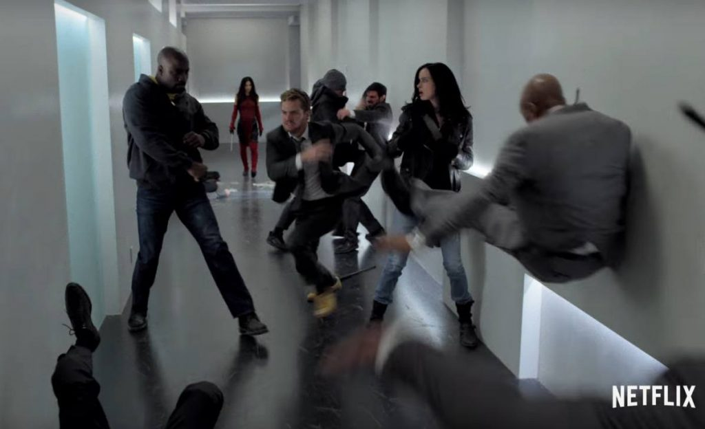 The Defenders fighting in a white hallway together