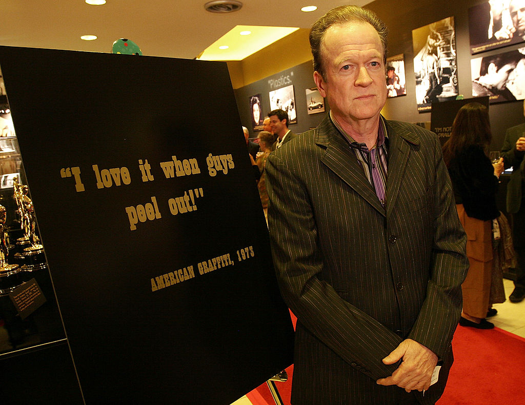 "Screenwriter Willard Huyck poses beside a poster that bears a famous line from his film ""American Graffiti"""