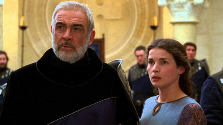 Sean Connery and Julia Ormond standing in front of a group of men and looking concerned off-screen in First Knight