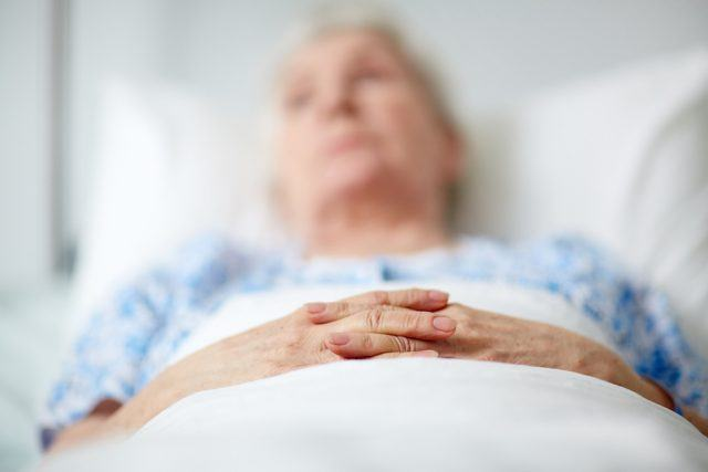 Senior woman in hospital bed with her hands together.